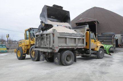 A Springfield front end loader drops salt into a truck ahead of a 2010 storm.