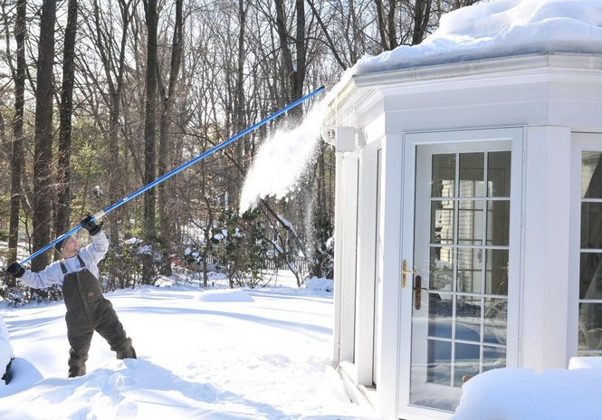 Kurtis Couture from Adam Quenneville Roofing Inc., uses a roof rake to clear the snow on the roof of this Longmeadow home in 2011.
