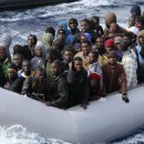 Migrants sit in a boat during a rescue operation by Italian navy off the coast of Sicily on Nov. 28, 2013. Italy is looking to revamp the way it handles the hundreds of thousands of migrants who arrive annually.