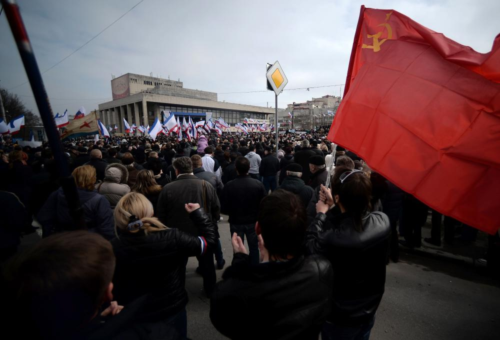 "A man holds a Soviet Union flag during a pro-Russia rally in Simferopol, Crimea's Lenin Square Sunday. In Kiev, Ukrainian Prime Minister Arseniy Yatsenyuk vows not to give ""an inch"" of territory to Russia."