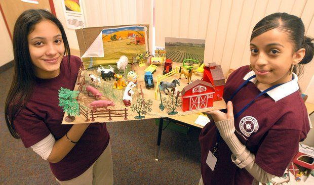 Holyoke, 2/3/07 -- From left, Holyoke Community Charter School students Mariah C. Santiago and Ashley E. DeJesus show a farm scene made by first grader Jomal Morales Ortiz as a first grade class project. The two were conducting tours of the school during the school's open house.