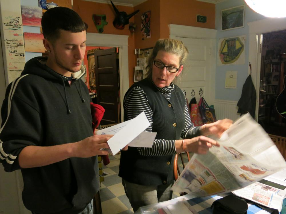 Lance Rice and Nina Rossi go through letters and clippings in her kitchen.