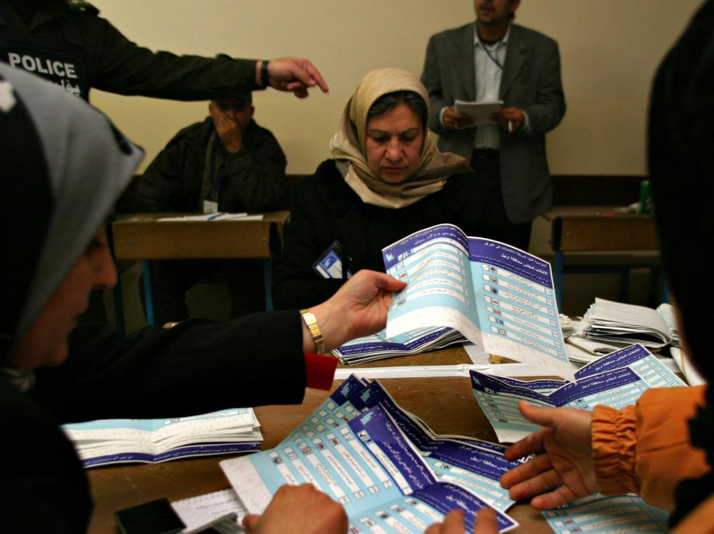 Election officials count ballots under the scrutiny of monitors in Iraq in 2005. Les Campbell from the National Democratic Institute worked as an election monitor during Iraq's 2005 elections, a job that came with a flak jacket and security detail.