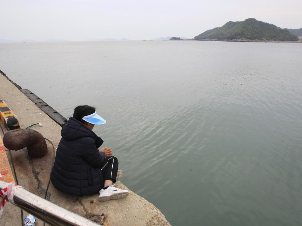 A relative of a passenger aboard the sunken Sewol ferry looks toward the sea as she awaits news on her missing loved one at a port in Jindo, South Korea, Saturday.