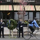A Boston Police honor guard is posted outside the Forum restaurant, the site of the second of two bombs that exploded near the finish line of the 2013 Boston Marathon, Tuesday.