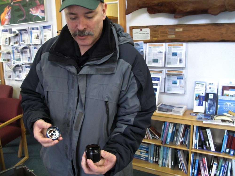 Scott Pegau a scientist in Cordova, Alaska, holds a sample of oil taken on Feb. 19 from Eleanor Island in the Prince William Sound.