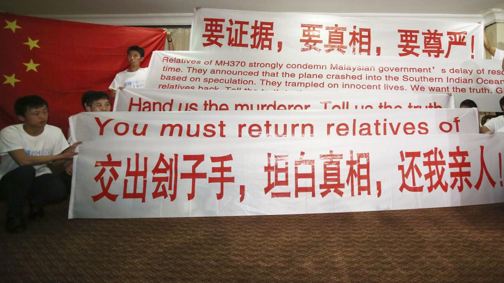 Newly arrived Chinese relatives of passengers of the missing Malaysia Airlines flight MH370 hold banners while talking to reporters at a hotel in Malaysia Sunday. The search continues for the jetliner that went missing three weeks ago.