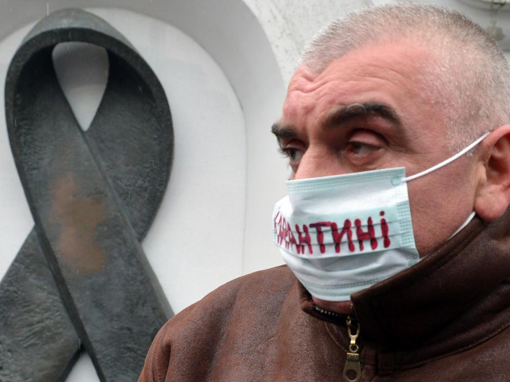 "The mask of this Kiev protester (at a 2012 demonstration demanding more funding for HIV treatment) reads ""quarantine."" There are only enough drugs to treat half the HIV patients in Ukraine."