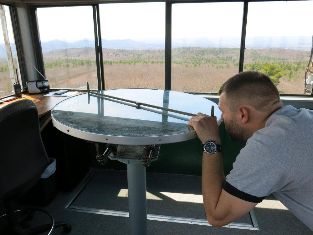 Firefighter Jesse Hanecek uses a device called an Alidade connected to a circular map, to calculate the location of a possible brush fire.