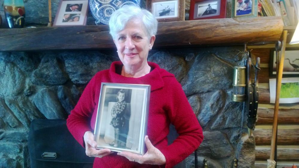 Dori Katz, holding a photo of herself as a little girl.