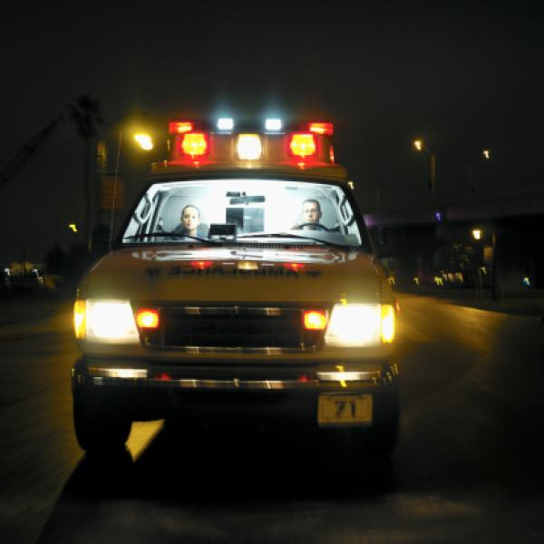An ambulance on the road at night with two young paramedics inside.
