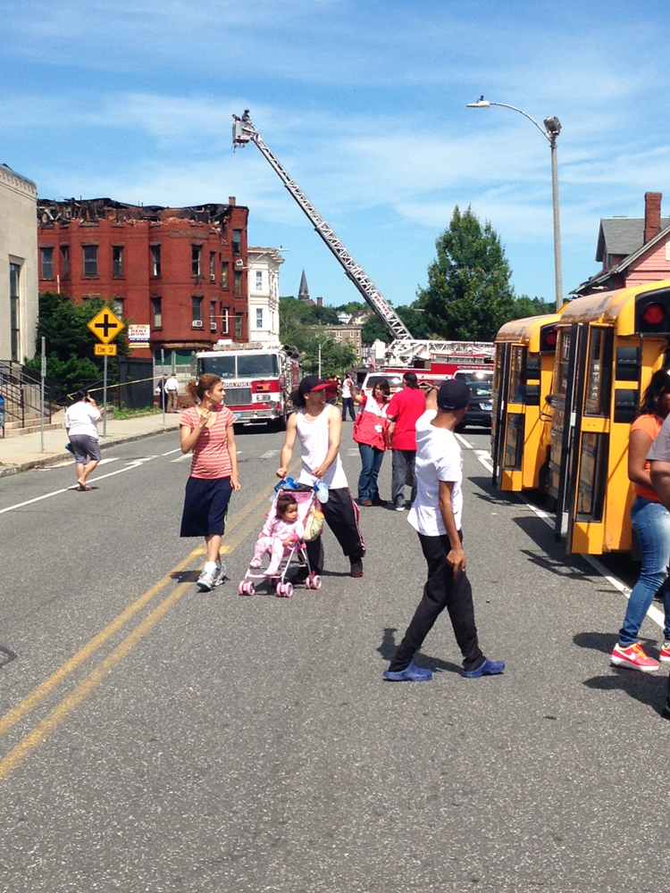 Residents of a burned out apartment building (in background) prepare to board shuttle buses to a temporary shelter at  War Memorial Building in Holyoke, Mass.  on June 16, 2014