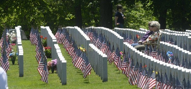 Some of the people attending the 2013 Memorial Day ceremony at the Massachusetts Veterans' Memorial Cemetery sit among the graves, usually near loved ones.