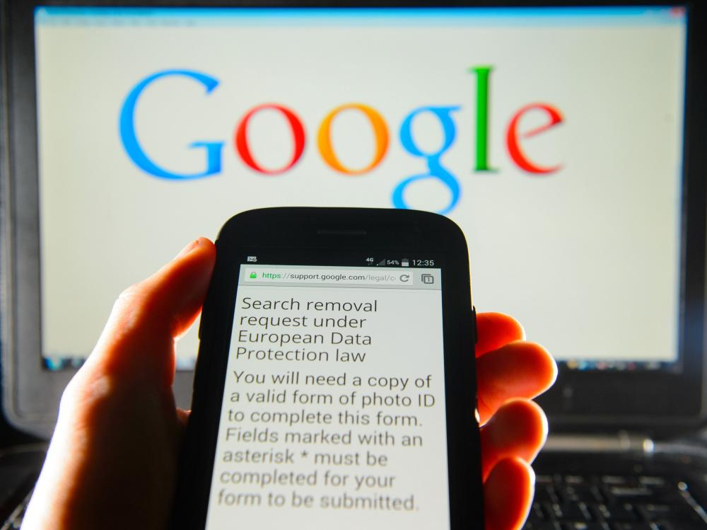 A Google search removal request is displayed on the screen of a smartphone in London. The company says it has received more than 70,000 takedown requests in the wake of a European court ruling.