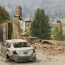 A burned-out car sits in front of a ruined house in this photo taken Sunday near Pateros, Washington. Large fires have destroyed hundreds of homes in the state this month.