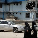People walk by a damaged police station in Mosul on July 15. The militants of the Islamic State are in control of the key city and have acted against former members of Saddam Hussein's regime who helped them drive out the Iraqi army last month.