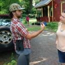Researcher Thom Bullock shows homeowner Sophia Pastori a Carolina Wren before releasing it.