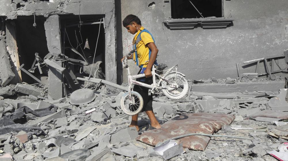A Palestinian youth carries a bicycle from the wreckage of a building hit in an Israeli strike in Rafah in the southern Gaza Strip Saturday. New violence killed dozens in Gaza after the collapse of a UN- and US- backed cease-fire, officials said.