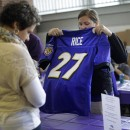 A Ravens fan trades in her Ray Rice jersey Friday after he was cut from the team over allegations of domestic abuse.