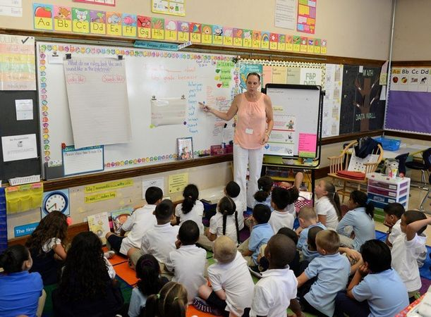 First grade teacher Elizabeth Gloss works with her students on the first day of classes at the Washington School in Springfield, Monday 25 August, 2014