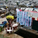 A woman washes clothes in a slum in Freetown.