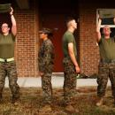 Katie Gorz (left) performs the ammo can lift next to male Marines as they go through the combat fitness test. The Marine Corps is experimenting with inserting some females into combat infantry roles that have historically been limited to males. At Camp Lejeune, female marines are undergoing the same training as their male counterparts for combat arms.
