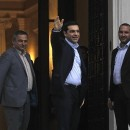 Newly sworn-in Greek Prime Minister Alexis Tsipras waves on his way to enter his new offices in Athens on Monday.