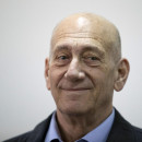 Former Israeli Prime Minister Ehud Olmert smiles as he waits in a court room in Jerusalem's District Court on Monday. The court later found him guilty of accepting bribes in a retrial of corruption charges.