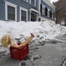 A fashion doll in a milk crate saves a parking space on a residential street in South Boston.