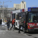 Riders enter and exit  a Pioneer Valley Transit Authority bus at UMass-Amherst