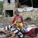 A woman and child rest in the open outside a destroyed building Sunday, a day after a major earthquake destroyed homes in Kumalpur village on the outskirts of Kathmandu, Nepal. Nine people reportedly died in the small village, including four children.