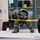 Springfield police, fire and bomb squad units responded to a bank robbery at the UnitedBank at the corner of State and Main after a robbery suspect left three suspicious packages behind. Here, firefighter Sean Walker, a member of the bomb squad, x-rays one of the suspicious packages at the front entrance of the bank.