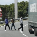 Migrants cross a road near the Eurotunnel in Coquelles, near Calais, France, Wednesday. A Sudanese man, between 25 and 30 years old, was killed by a truck as up to 1,500 migrants tried to force their way into the tunnel, officials say.