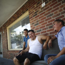 Joel Munguia (center), owner of Chino's, a barbershop in Kenner, La., sits with his nephew, Waldyn Munguia (left), as they have a laugh outside on the waiting benches at the shop. Munguia came to New Orleans from Honduras in 2005 after Katrina and opened his dream shop for Latino hairstyles in 2012.