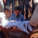 Abdullah Kurdi, holds the body of his 3-year-old son, Aylan Kurdi, during the burial of the boy, his brother Friday and his mother at a funeral in Kobane, Syria.