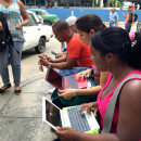 Havana residents huddle in front of the Habana Libre hotel, trying to log onto the Internet.