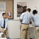 Attending a new charter school, Jann Peña has had to get used to wearing a uniform daily and being in class an hour and a half later each afternoon. Here, he watches classmates during a group project.