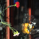 A flower is placed inside a bullet hole in the window of Le Carillon restaurant in tribute to the victims of the terror attacks on November 15 in Paris, France.
